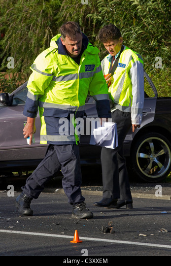 Police crash investigators at the scene of a collision between a bus and a car - Stock Image