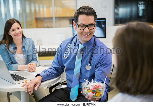 Pediatrician giving candy to girl in clinic office - Stock Image