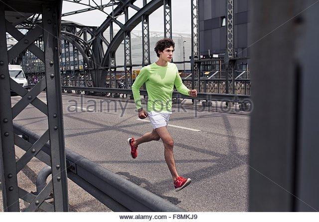 Young man running across urban bridge - Stock-Bilder