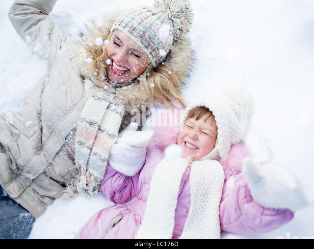Happy parent and kid lying on snow in winter outdoor - Stock Image
