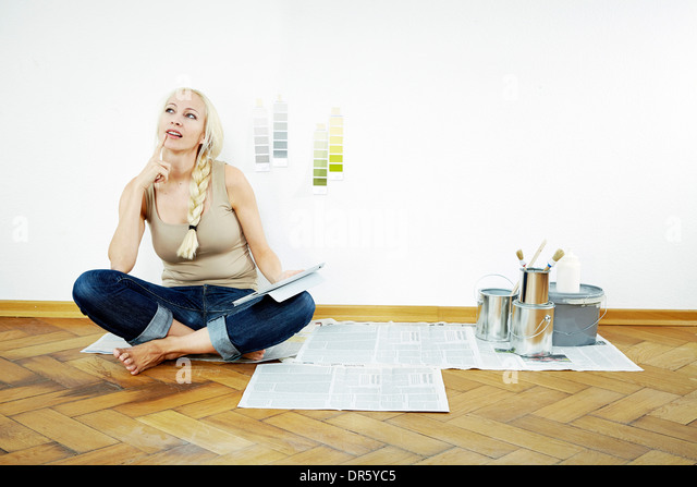 Young woman sits on parquet floor, color samples on the wall, Munich, Bavaria, Germany - Stock Image