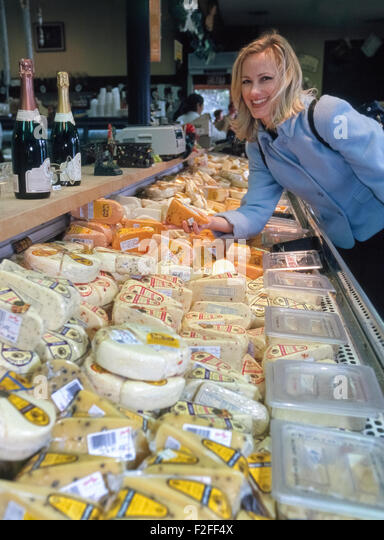 A woman happily chooses from a wide variety of cheeses at the well-known Sonoma Cheese Factory in Sonoma, California, - Stock Image