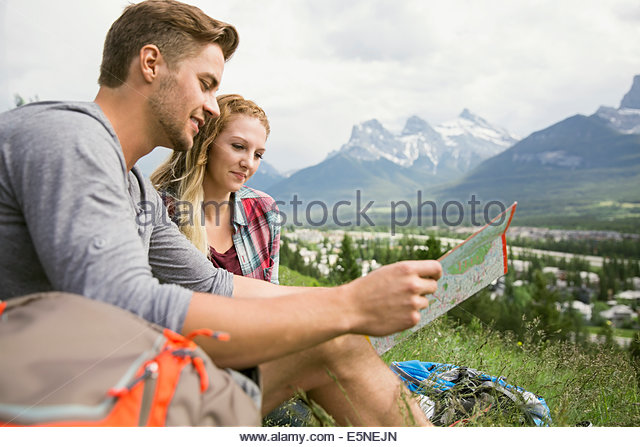 Couple looking at map in grass near mountains - Stock Image