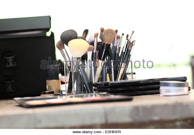 Different makeup brushes on the wood table - Stock Image