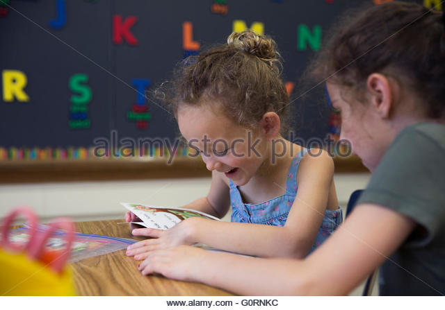 young girls reading in a classroom - Stock Image