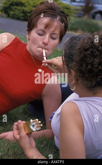 girl lighting her friend's cigarette - Stock Image