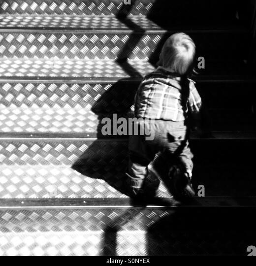 Boy toddler climbing stairs - Stock Image