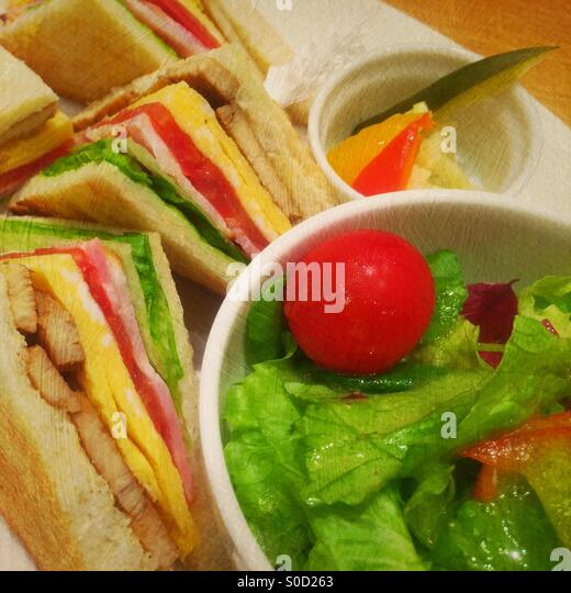 Delicious sandwiches with chicken, egg, tomatoes, lettuce and ham with side serving of pickled vegetables and green - Stock Image