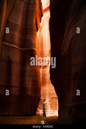 small little man person touching tall long high rock wall canyon dark light day low down brown layers lines travel - Stock Image