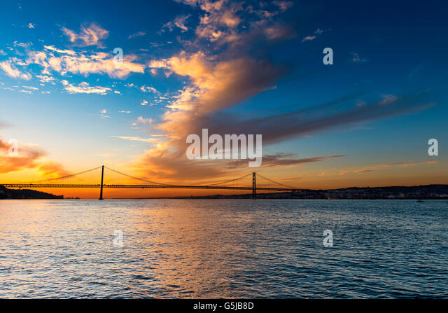 View of the bridge over the Tagus River in Lisbon, Portugal, at sunset - Stock-Bilder