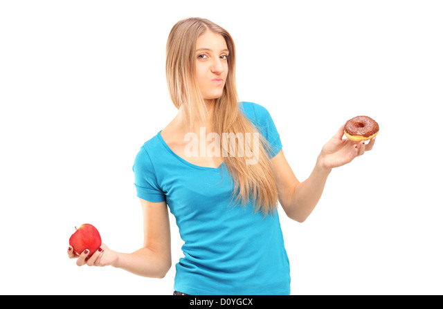 Young doubtful female holding a red apple and donut trying to decide which one to eat - Stock Image