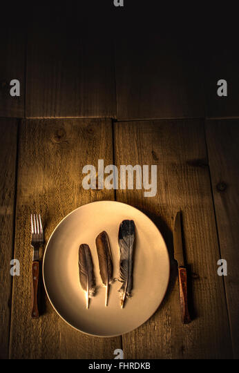 still life with a feathers on a plate and fork and knife on wooden table - Stock Image