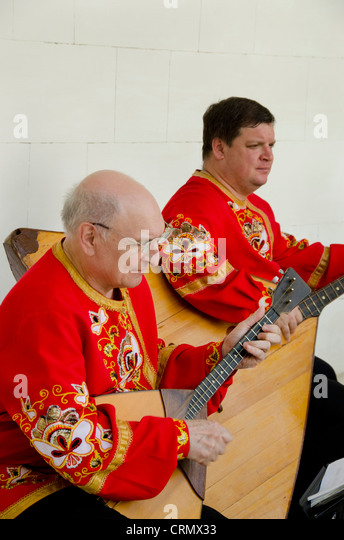 Ukraine, Yalta, Livadia Palace. Ukrainian folkloric show. Men playing Russian three-stringed balalaika. - Stock Image