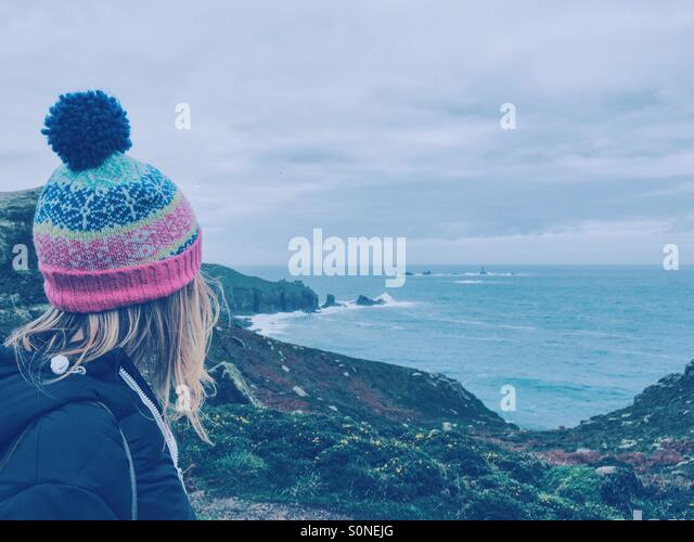 Woman in woolly hat looking out to sea - Stock Image