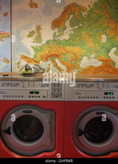 Washing machines in a laundrette with a map of Europe behind. The Laundromat Cafe, a hip combined cafe/laundrette - Stock Image