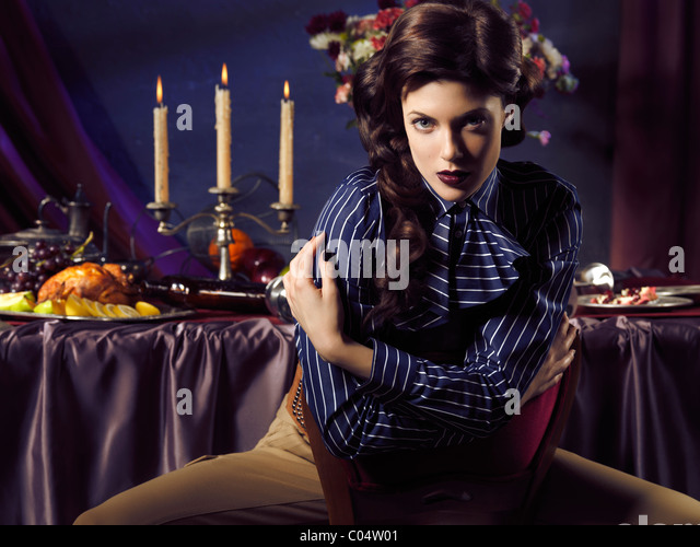 Artistic high fashion photo of a beautiful woman sitting at a table with remains of a festive dinner - Stock-Bilder