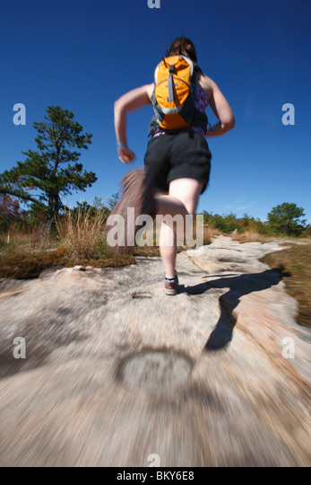 Blur motion of woman running on a rocky trail in North Carolina. - Stock Image
