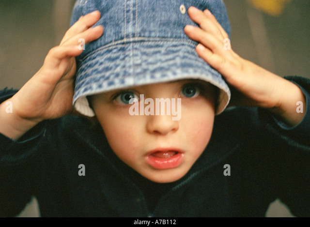 close up crop of a small boy holding his denim hat on his head - Stock Image