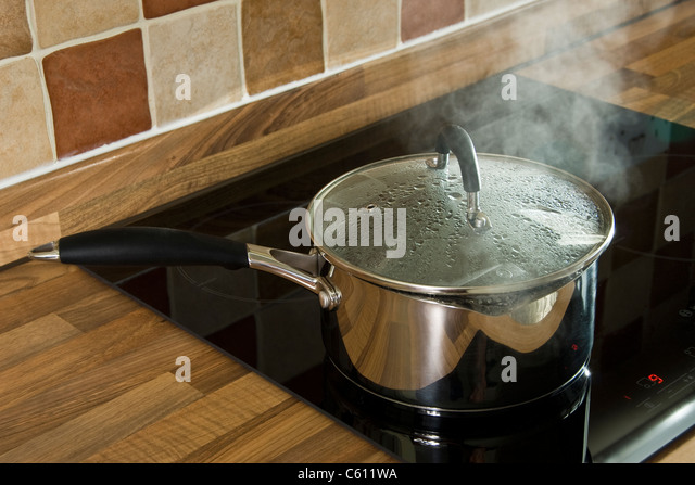 Stainless steel saucepan of boiling water, with glass lid, on an induction hob. - Stock Image