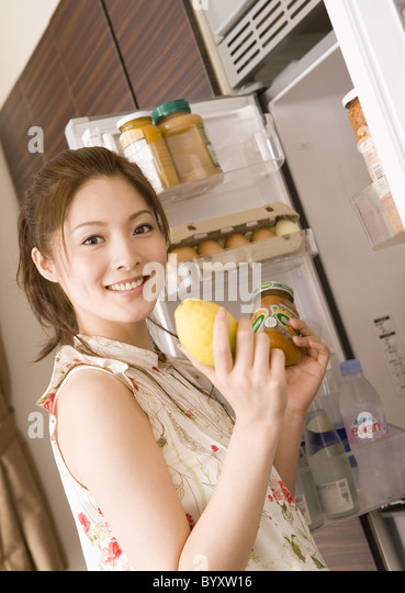 Woman selecting foods from fridge - Stock Image