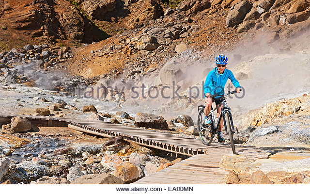 Mature female cyclist riding hybrid bike at geothermal site, Krysuvik, Reykjanes, Iceland - Stock Image