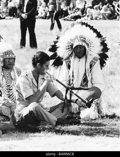 Prince Charles attending a Blackfoot Indian ceremony at Calgary Canada puffs a peace pipe watched by medicine man - Stock Image