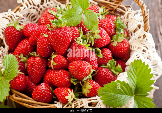Strawberries in basket on rustic wooden background - Stock Image