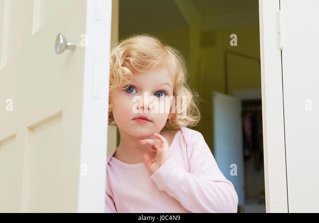 Female toddler peering from door - Stock Image
