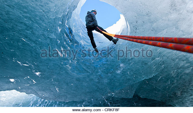 Climber abseiling into ice cave - Stock Image