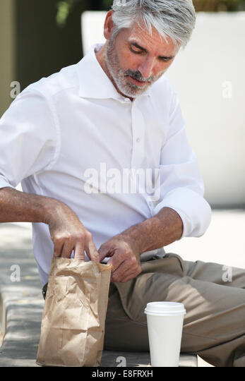 Businessman having lunch break outdoors - Stock Image