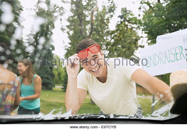 Portrait of smiling man washing car windshield - Stock Image