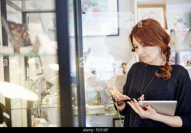 A mature woman holding a digital tablet, stock-taking in a small shop. - Stock Image