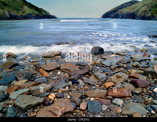 View out across pebble-strewn Ceibwr Bay towards the Irish Sea. - Stock Image