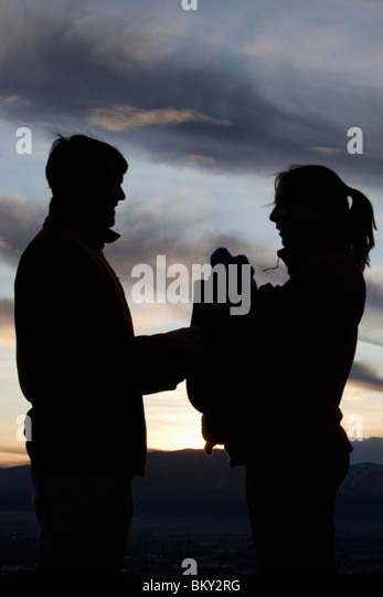 Mother,father and baby in front carrier silhouetted against beautiful sunset. - Stock Image