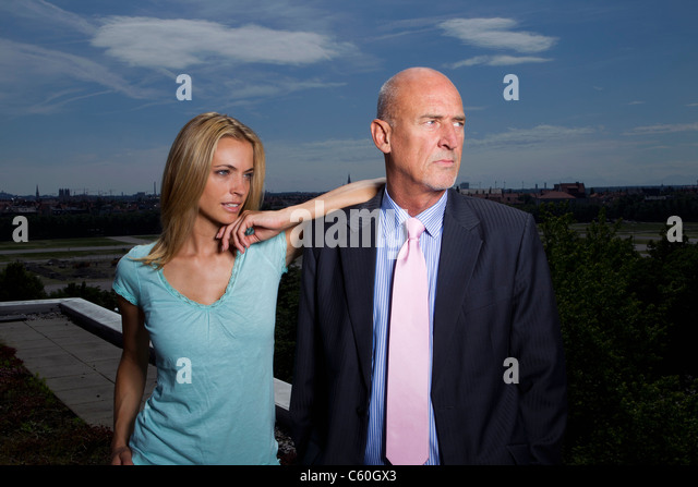 Business people standing on roof - Stock Image