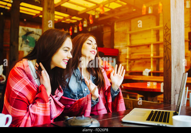two girls watching something in laptop - Stock-Bilder
