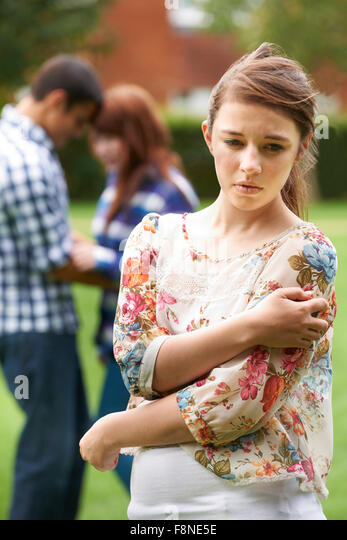 Lonely Jealous Teenage Girl With Romantic Couple In Background - Stock-Bilder