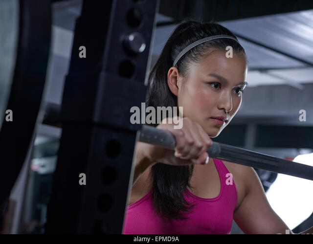 Young woman doing weightlifting with barbell - Stock Image