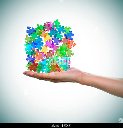 a man hand with a pile of puzzle pieces of different colors as the symbol for the autism awareness - Stock Image