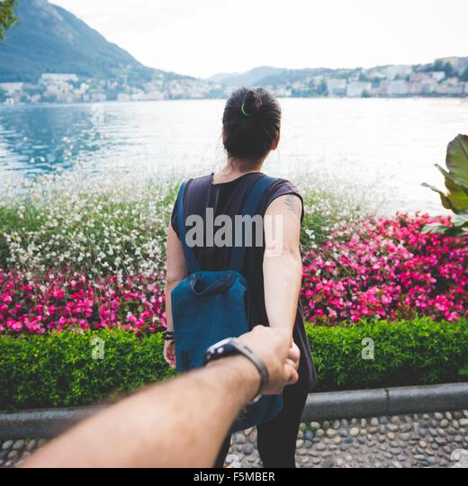 Mid adult tourist couple holding hands at Lake Lugano, Switzerland - Stock-Bilder