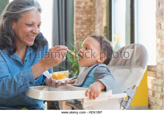 Hispanic grandmother feeding baby grandson in high chair - Stock Image