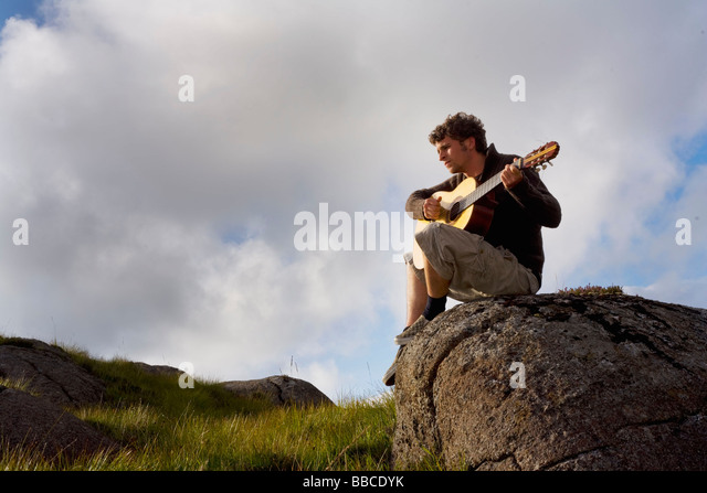 Young man playing guitar in landscape - Stock Image
