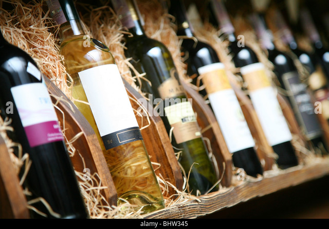 Closeup shot of wineshelf. Bottles lay over straw. - Stock-Bilder