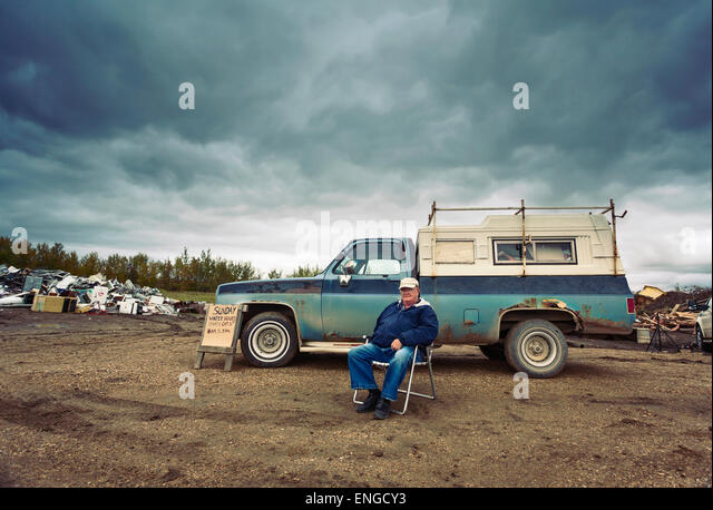A mature man seated in a chair by his pick up truck. Piles of waste, scrap metal and wood objects. - Stock Image