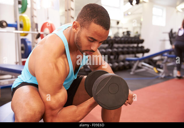 Man exercising with dumbbells at a gym, horizontal shot - Stock Image