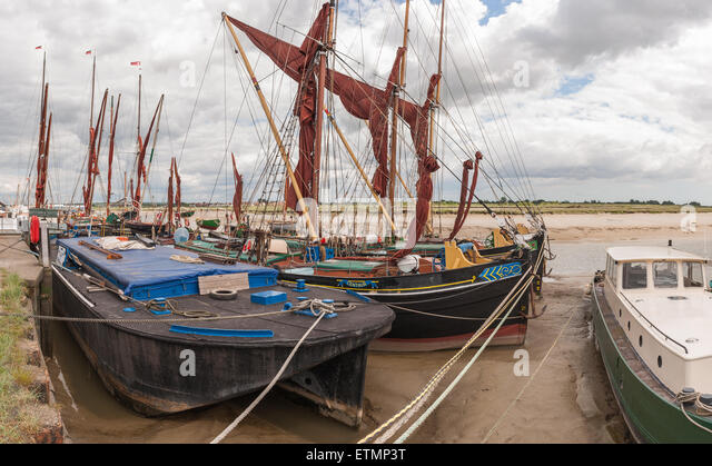 Moored old sailing barges at the Hythe Quay at lowtide supported by silt and mud sandy beds of river Chelmer - Stock Image