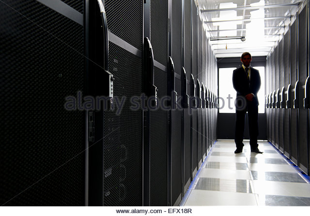 Manager standing in aisle of storage cabinets in data center - Stock Image