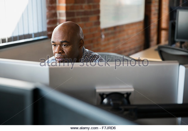 Businessman working at computers in office - Stock Image