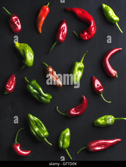 Pattern of small colorful hot chili peppers on black background - Stock Image