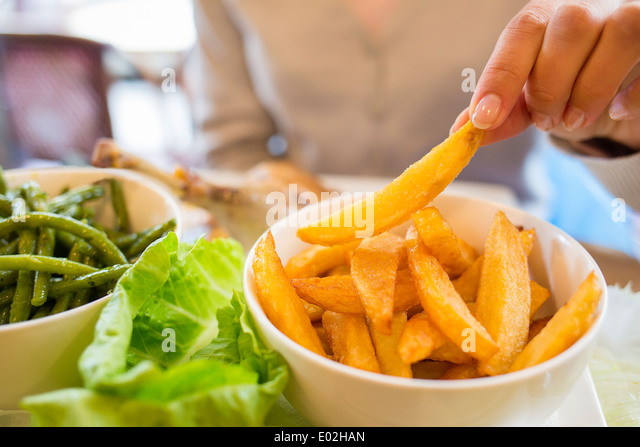 Female eating meat close-up finger bar indoor - Stock Image